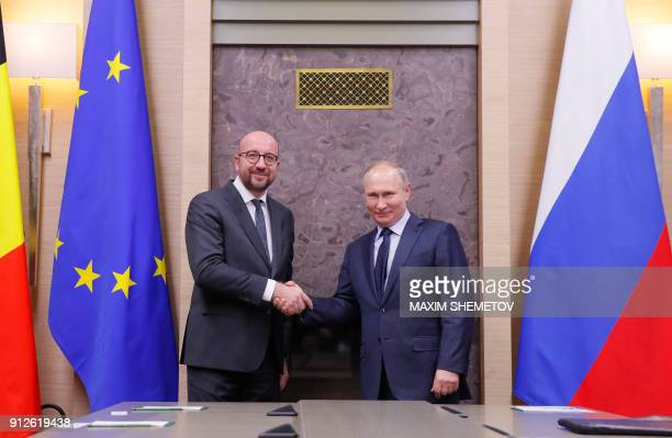 Russian President Vladimir Putin shakes hands with Belgian Prime Minister Charles Michel during a meeting at the NovoOgaryovo state residence outside...