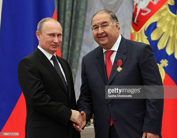 Russian President Vladimir Putin shakes hands with billionaire Alisher Usmanov during an awards ceremony at the Kremlin October 29 2013 in Moscow...