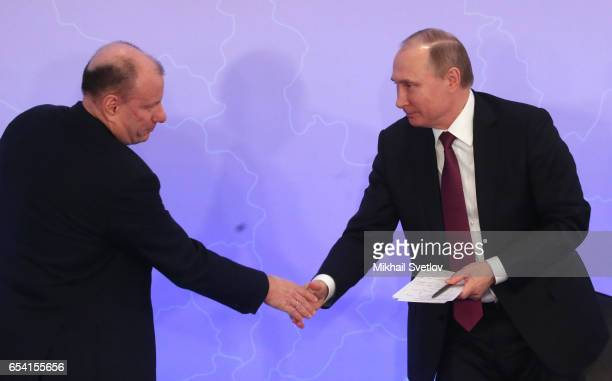 Russian President Vladimir Putin shakes hands with billionaire and businessman Vladimir Potanin during the plenary session of the Congress of Russian...