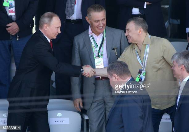 Russian President Vladimir Putin shakes hands with billionaire and businessman Arkady Rotenberg as his brother Boris Rotenberg looks on during the...