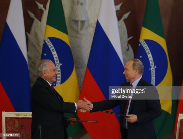 Russian President Vladimir Putin shakes hands with Brazilian President Michel Temer during their meeting at the Grand Kremlin Palace in Moscow Russia...