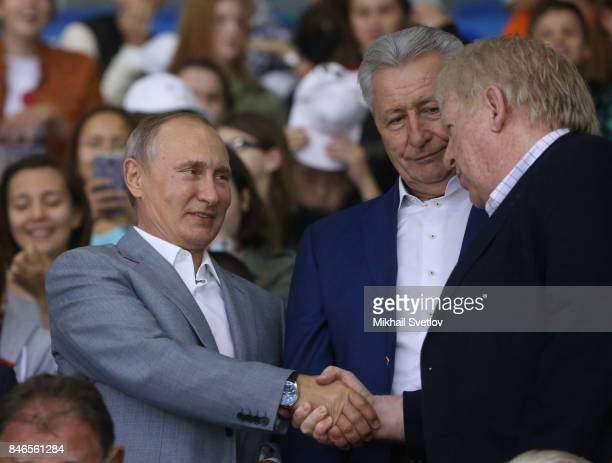Russian President Vladimir Putin shakes hands with Canadian former ice hockey player Pat Stapleton while visiting a children's ice hockey match at...
