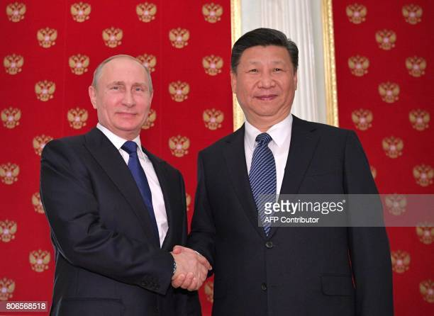 Russian President Vladimir Putin shakes hands with China's President Xi Jinping during an informal meeting in the Kremlin in Moscow on July 3 as Xi...