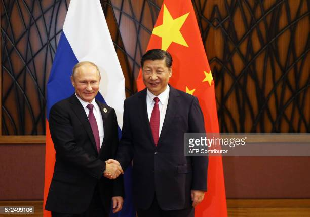 Russian President Vladimir Putin shakes hands with China's President Xi Jinping during a meeting on the sidelines of the AsiaPacific Economic...