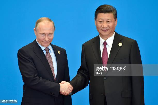 Russian President Vladimir Putin shakes hands with Chinese President Xi Jinping during the welcome ceremony for the Belt and Road Forum at the...