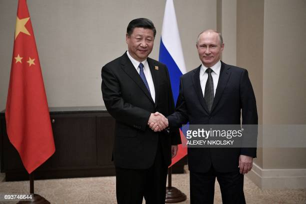 Russian President Vladimir Putin shakes hands with Chinese President Xi Jinping during their meeting in Astana on June 8, 2017. / AFP PHOTO / SPUTNIK...
