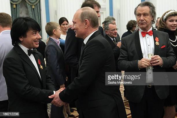 Russian President Vladimir Putin shakes hands with fashion designer Valentin Yudashkin as painter Alexander Shilov looks on during an awards ceremony...