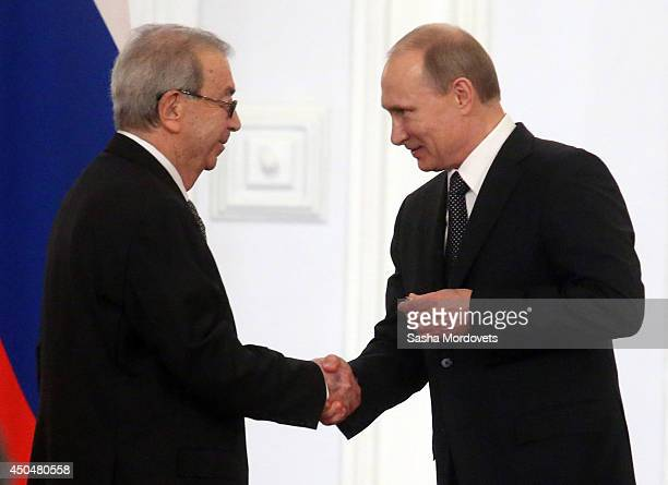 Russian President Vladimir Putin shakes hands with Former Prime Minister Yevgeny Primakov during the State Awards Ceremony during celebration of the...