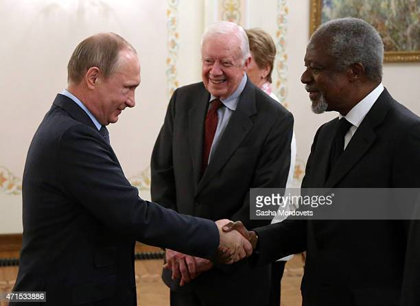 Russian President Vladimir Putin shakes hands with former UN SecretaryGeneral Kofi Annan as former USPresident Jimmy Carter looks on during a meeting...
