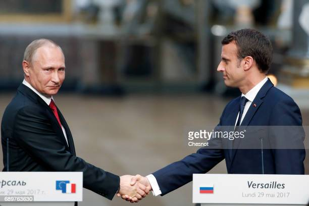 Russian President Vladimir Putin shakes hands with French President Emmanuel Macron after a joint press conference at 'Chateau de Versailles' on May...