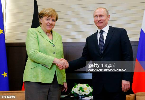 Russian President Vladimir Putin shakes hands with German Chancellor Angela Merkel during a meeting at the Bocharov Ruchei state residence in Sochi...