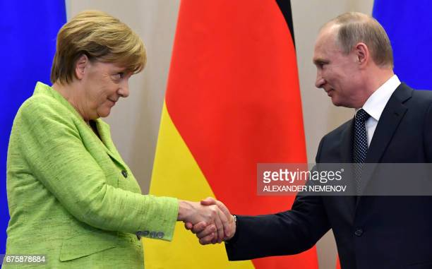 Russian President Vladimir Putin shakes hands with German Chancellor Angela Merkel after a press conference following their meeting at the Bocharov...