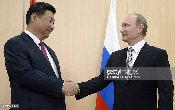 Russian President Vladimir Putin shakes hands with his China's counterpart Xi Jinping during their meeting in Ufa on July 8 2015 ahead of the start...