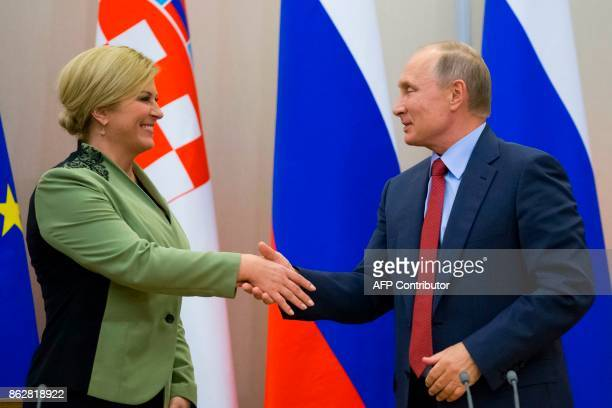 Russian President Vladimir Putin shakes hands with his Croatian counterpart Kolinda GrabarKitarovic at the end of their joint press conference...