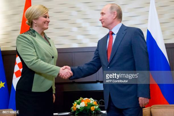 Russian President Vladimir Putin shakes hands with his Croatian counterpart Kolinda GrabarKitarovic during their meeting at the Bocharov Ruchei state...