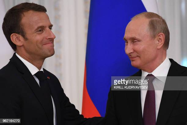 Russian President Vladimir Putin shakes hands with his French counterpart Emmanuel Macron at the end of a joint press conference following their...