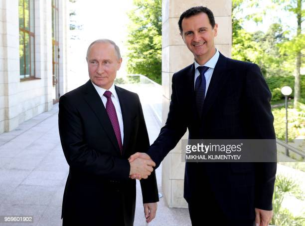 TOPSHOT Russian President Vladimir Putin shakes hands with his Syrian counterpart Bashar alAssad during their meeting in Sochi on May 17 2018