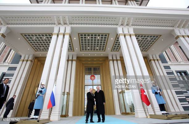 Russian President Vladimir Putin shakes hands with his Turkish counterpart Recep Tayyip Erdogan on December 1 2014 at the entrance of the new...
