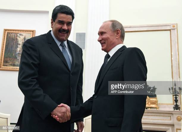 Russian President Vladimir Putin shakes hands with his Venezuelan counterpart Nicolas Maduro during a meeting at the Kremlin in Moscow on October 4...