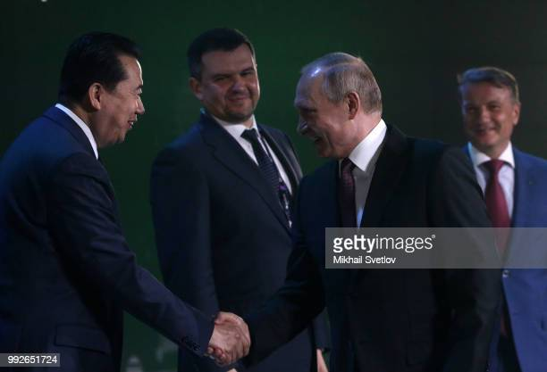 Russian President Vladimir Putin shakes hands with Interpol Director Meng Hongwei as Deputy Prime Minister Igor Akimov and CEO and Charman of...