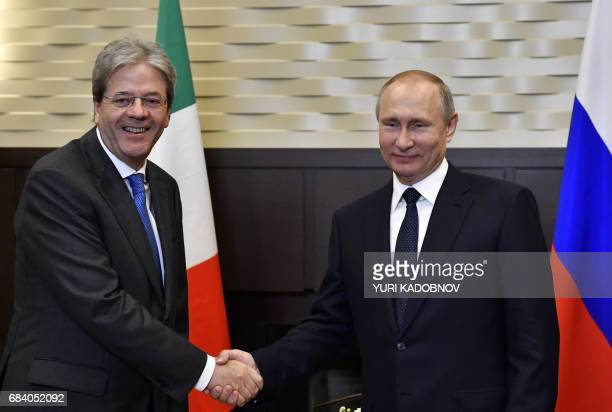 Russian President Vladimir Putin shakes hands with Italian Prime Minister Paolo Gentiloni during a meeting at the Bocharov Ruchei state residence in...