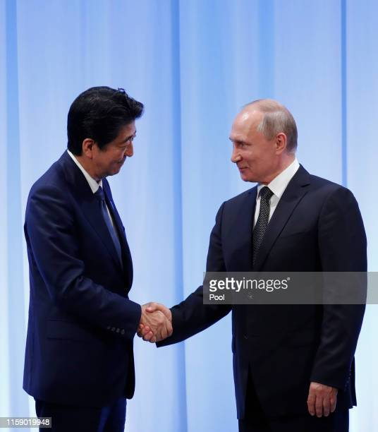 Russian President Vladimir Putin shakes hands with Japanese Prime Minister Shinzo Abe at their news conference at G20 leaders summit on June 29, 2019...
