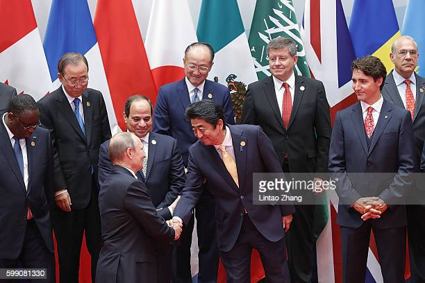 Russian President Vladimir Putin shakes hands with Japanese Prime Minister Shinzo Abe before a group photo at the Hangzhou International Expo Center...