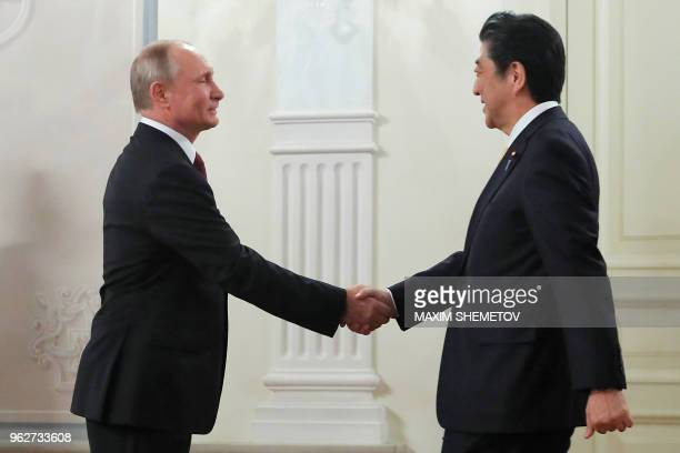 Russian President Vladimir Putin shakes hands with Japanese Prime Minister Shinzo Abe before the opening ceremony of the crosscultural year of Russia...