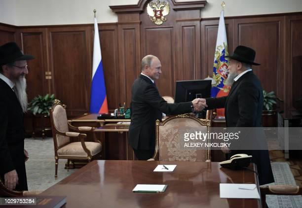 Russian President Vladimir Putin shakes hands with President of the Federation of Jewish Communities Alexander Boroda as Chief Rabbi of Russia Berel...