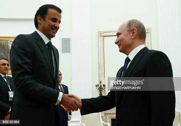 Russian President Vladimir Putin shakes hands with Qatar's Emir Sheikh Tamim bin Hamad alThani during a meeting at the Kremlin in Moscow on March 26...