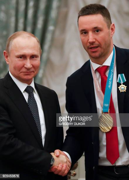 Russian President Vladimir Putin shakes hands with Russian ice hockey player and gold medalist of the 2018 Pyeongchang Winter Olympic Games Ilya...