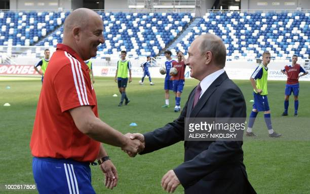 Russian President Vladimir Putin shakes hands with Russia's national football team head coach Stanislav Cherchesov as he visits the Kaliningrad...
