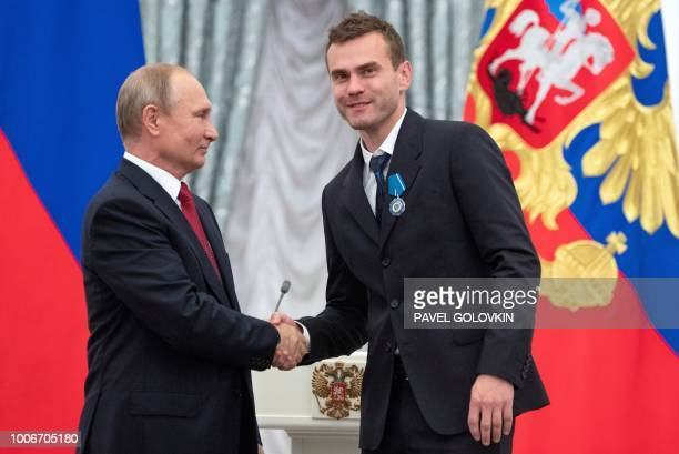 Russian President Vladimir Putin shakes hands with Russia's national football team goalkeeper Igor Akinfeev during an awards ceremony for the team at...