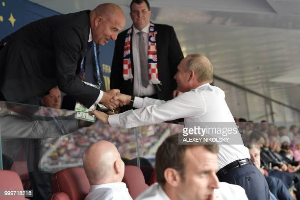 Russian President Vladimir Putin shakes hands with Russia's national football team coach Stanislav Cherchesov during the Russia 2018 World Cup final...