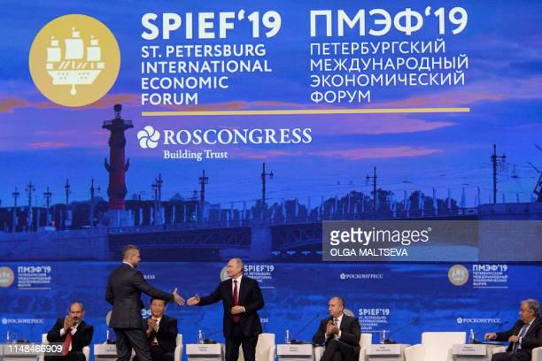 Russian President Vladimir Putin shakes hands with Slovak Prime Minister Peter Pellegrini during a plenary session of the St Petersburg International...