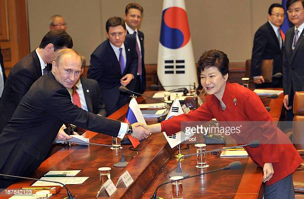 Russian President Vladimir Putin shakes hands with South Korean President Park Geun-Hye during their meeting at the presidential Blue House on...