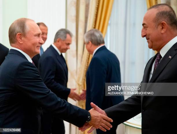 Russian President Vladimir Putin shakes hands with Turkish Foreign Minister Mevlut Cavusoglu prior to their meeting at the Kremlin in Moscow on...