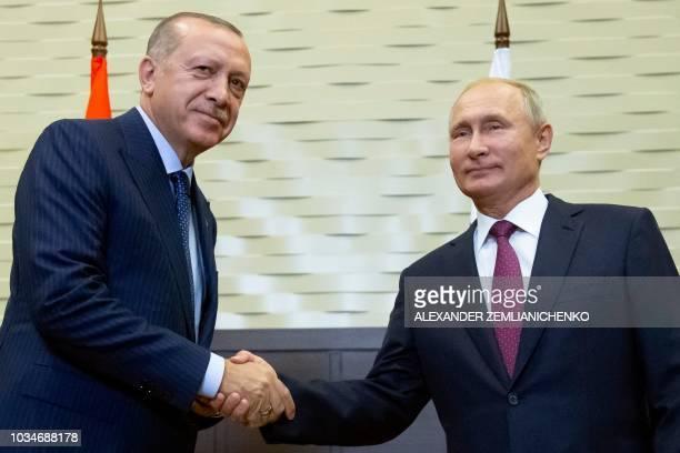Russian President Vladimir Putin shakes hands with Turkish President Recep Tayyip Erdogan during their meeting in the Bocharov Ruchei residence in...