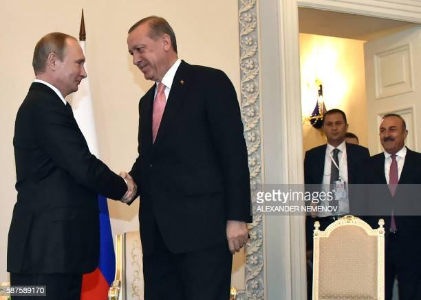 Russian President Vladimir Putin shakes hands with Turkish President Recep Tayyip Erdogan as Turkish Foreign Affairs Minister Mevlut Cavusoglu looks...