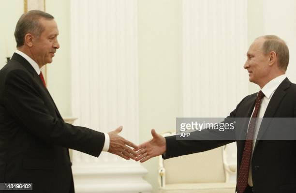 Russian President Vladimir Putin shakes hands with Turkish Prime Minister Recep Tayyip Erdogan during their meeting to discuss differences on Syria...