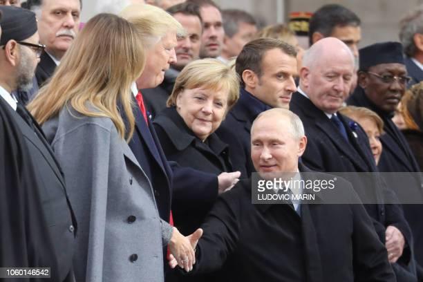 Russian President Vladimir Putin shakes hands with US First Lady Melania Trump next to US President Donald Trump and German Chancellor Angela Merkel...