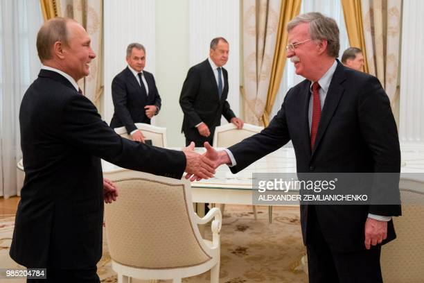 Russian President Vladimir Putin shakes hands with US National security advisor John Bolton during their meeting in the Kremlin in Moscow on June 27...