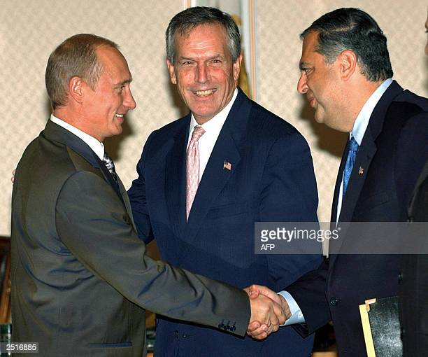 Russian President Vladimir Putin shakes hands with US Secretary of Energy Spencer Abraham as US Secretary of Commerce Don Evans smiles at his...
