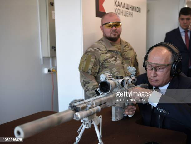 Russian President Vladimir Putin shoots a Chukavin sniper rifle during a visit to the military Patriot Park in Kubinka outside Moscow on September 19...
