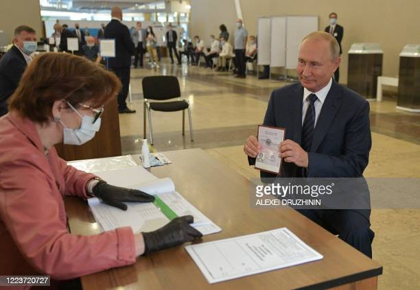 TOPSHOT Russian President Vladimir Putin shows his passport to a member of a local electoral commission as he arrives to cast his ballot in a...