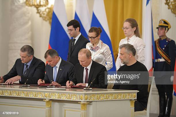 Russian President Vladimir Putin signs the treaty of annexation of Crimea and formation of new federal districts in a meeting with Prime Minister of...