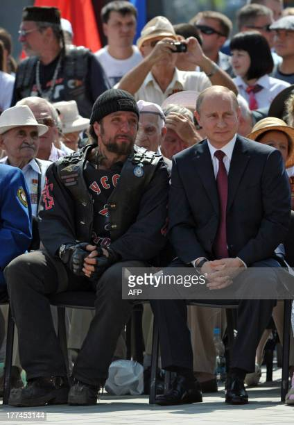 Russian President Vladimir Putin sits next to Russian Bikers' Association president Alexander Zaldostanov as they attend the opening ceremony of the...