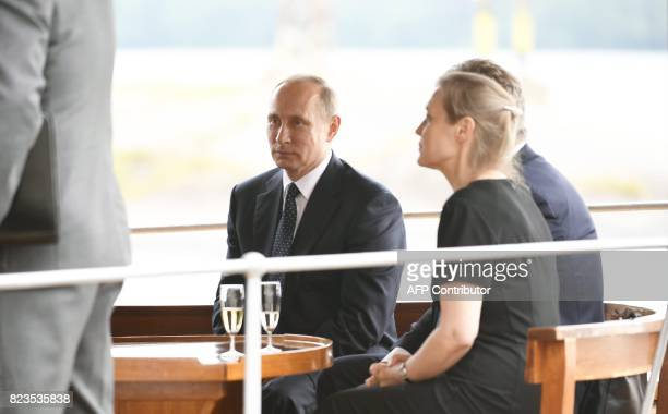 Russian President Vladimir Putin sits onboard the passenger steamer S/S Saimaa as he arrives at the Castle of Olavinlinna in Savonlinna Eastern...