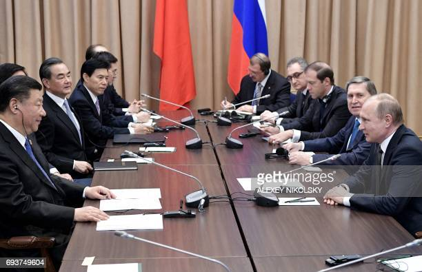 Russian President Vladimir Putin sits with members of his delegation as he speaks with Chinese President Xi Jinping and members of his delegation...