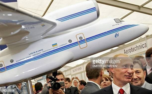 Russian President Vladimir Putin smiles near a model of Ukrainian AN-74tk-200 jet during an opening ceremony of the International Aviation and Space...